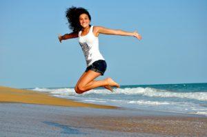 海岸でジャンプしている女性