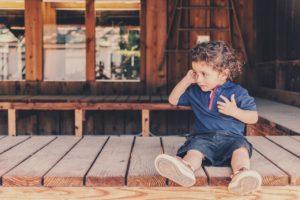 耳に手を当て座る子供