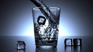 氷の入ったコップに水を注ぐ