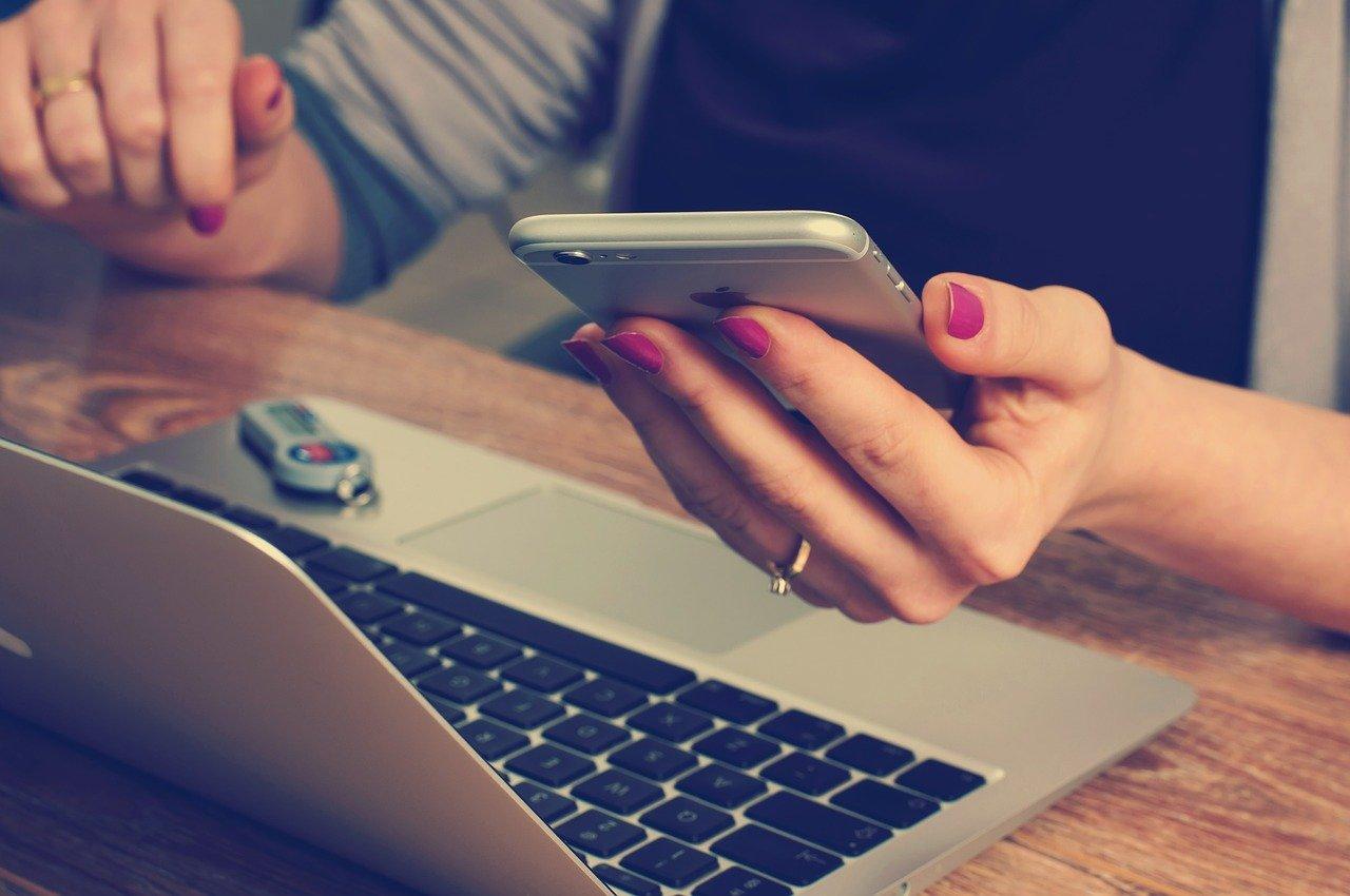 パソコンとスマホを手に取る女性